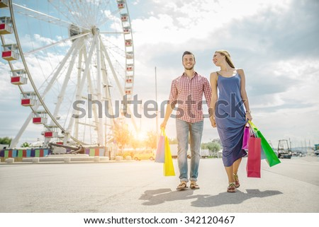 Happy couple laughing and walking while shopping - Young attractive boyfriend and girlfriend with shopping bags outdoors - stock photo