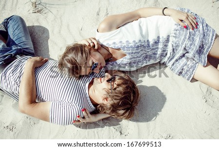 happy couple laying together on sand  - stock photo
