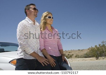 Happy couple leaning on car and looking away - stock photo