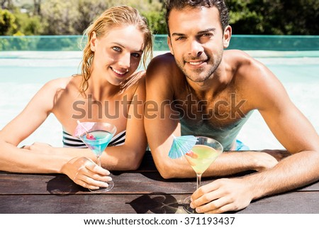 Happy couple leaning on pool edge and holding cocktails in a sunny day - stock photo