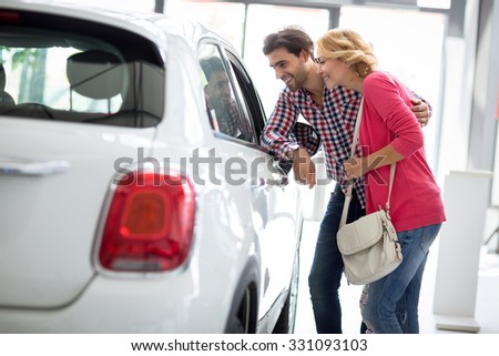 Happy couple looking a new car in  car dealership saloon - stock photo