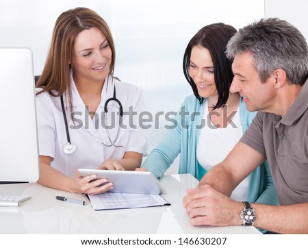 Happy Couple Looking At Digital Tablet Held By Doctor - stock photo