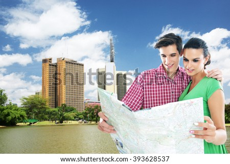 Happy couple looking at map in Nairobi city .Shallow doff - stock photo
