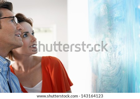 Happy couple looking at modern painting in art gallery - stock photo