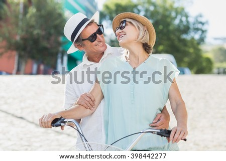 Happy couple looking each other while riding bicycle in city - stock photo