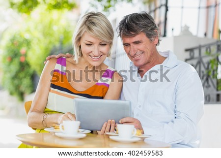 Happy couple looking into tablet at cafe - stock photo