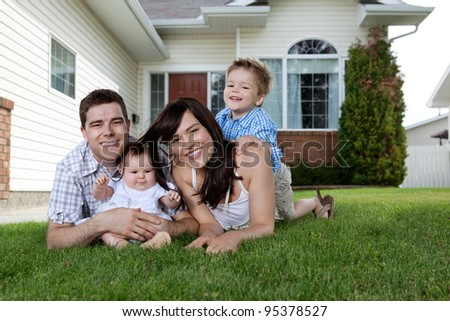 Happy couple lying down on grass with their adorable children - stock photo