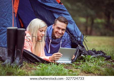 Happy couple lying in their tent using tablet in the countryside - stock photo