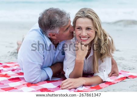 Happy couple lying on a blanket and kissing at the beach - stock photo