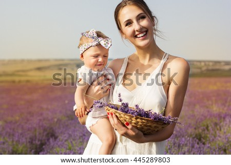 Happy couple mom is having fun with her baby girl in purple lavender field, summer time - stock photo