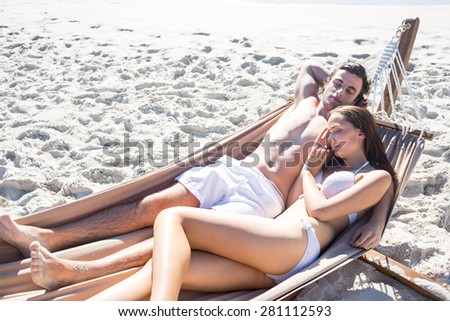 Happy couple napping together in the hammock at the beach - stock photo