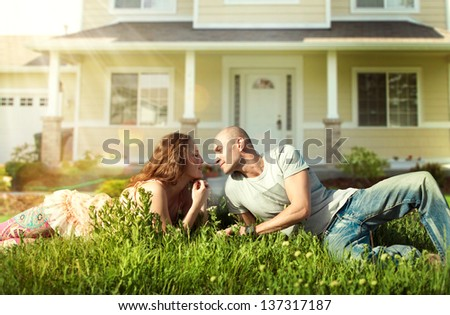 Happy Couple near their Home.Smiling Family outdoor.Real Estate - stock photo