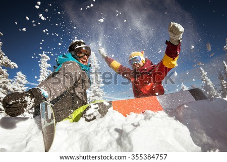 Happy couple of snowboarders having fun sitting in snowdrift with snowboards and   - stock photo