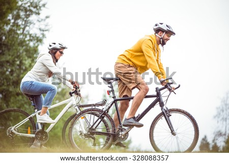 Happy couple on a bike ride in the countryside - stock photo