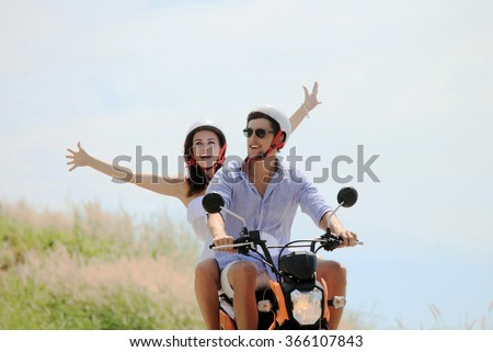 Happy couple on a scooter at summer vacation - stock photo