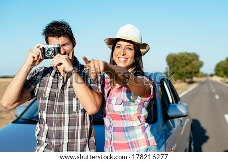 Happy couple on car roadtrip tourism. Man and woman on road travel vacation taking photos with retro camera. - stock photo