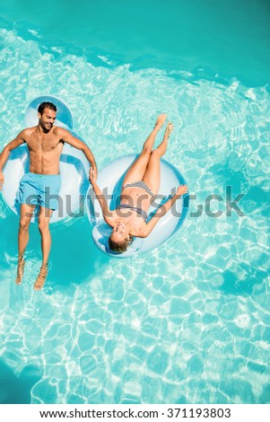 Happy couple on lilos in the pool - stock photo