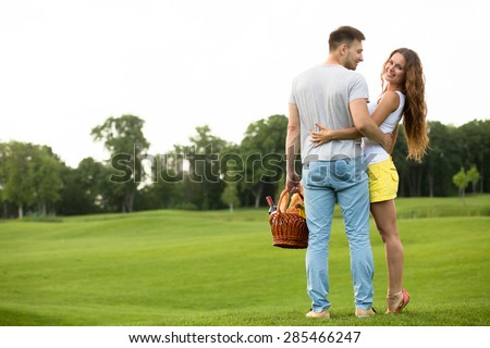 Happy couple on romantic picnic having rest. Young man with her lovely woman with basket full of food and drink. - stock photo