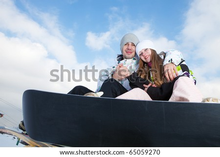 Happy couple on snowboards at winter - stock photo
