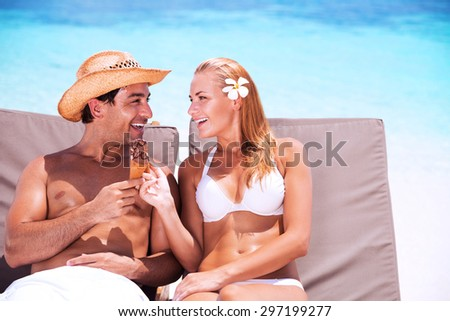 Happy couple on the beach sitting on sunbed and eating tasty sweet ice cream, with love looking on each other, enjoying romantic summer vacation  - stock photo