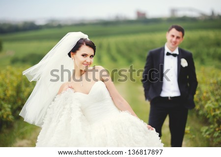 Happy couple on wedding day in summer field - stock photo
