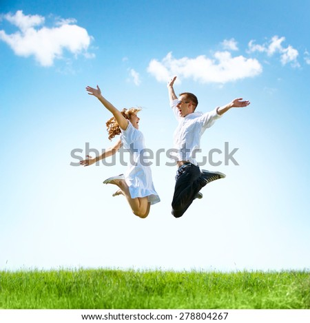 Happy Couple Outdoor. Jumping Family on Green Field. Freedom concept. Free. Jumping People. Fun - stock photo