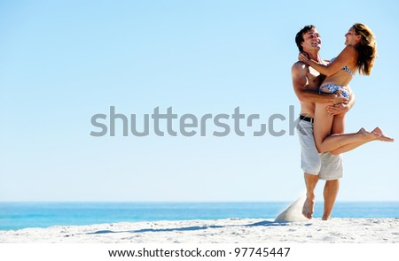 Happy couple playing on the beach, summer spin and hug embrace - stock photo