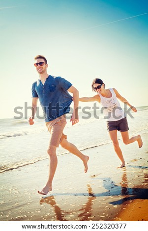 happy couple playing on the seashore - stock photo
