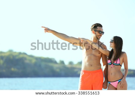 Happy couple pointing at the beach, outdoors - stock photo
