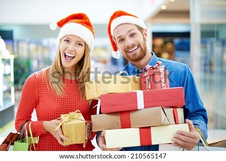 Happy couple posing with Christmas presents - stock photo
