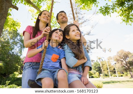 Happy couple pushing kids on swing in playground - stock photo