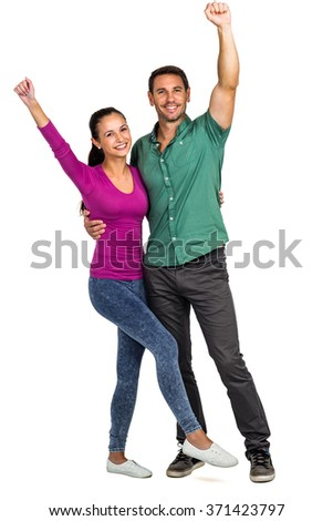Happy couple raising fists on white screen - stock photo