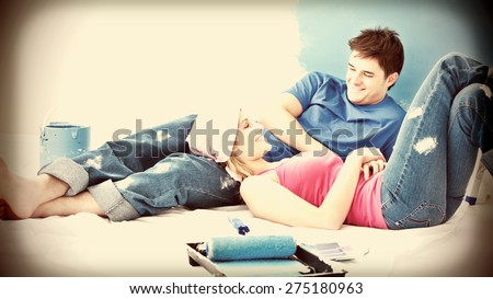 Happy couple relaxing after painting a room in their new house - stock photo