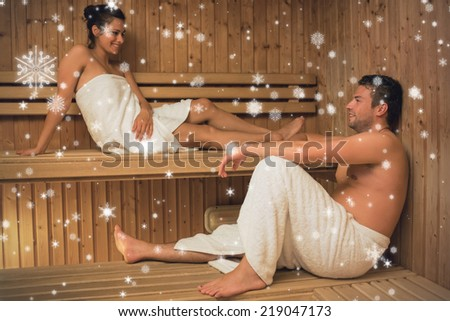 Happy couple relaxing in a sauna and chatting against snow falling - stock photo