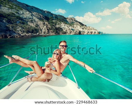 Happy couple relaxing on a boat at sea. Luxury holiday on a yacht. - stock photo