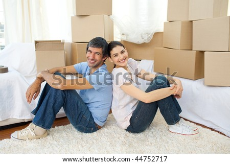 Happy couple relaxing sitting on the floor while moving house - stock photo