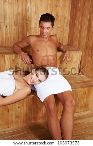Happy couple relaxing together in a sauna - stock photo