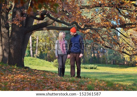Happy couple resting in autumn park holding hands - stock photo