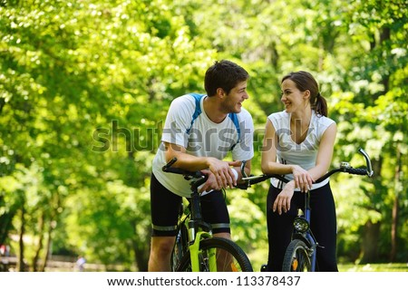 Happy couple ride bicycle outdoors, health lifestyle fun love romance concept - stock photo