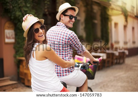 Happy couple riding a bicycle in the city street  - stock photo