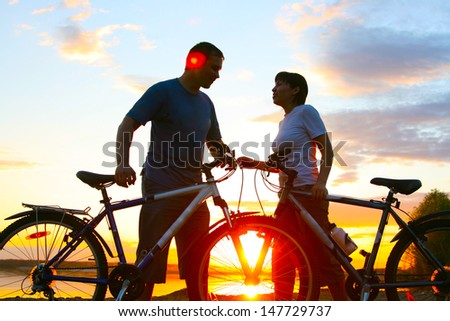 Happy couple riding bicycles outside, healthy lifestyle fun concept. silhouette at sunset panoramic Copy space for inscription  - stock photo