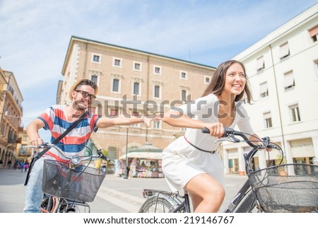 Happy couple riding bikes in the city - stock photo