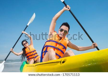 Happy couple rowing in kayak - stock photo