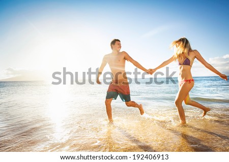 Happy couple running on a tropical beach in the ocean at sunset - stock photo