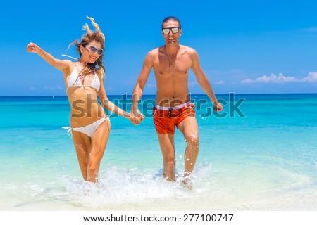 happy couple running on the beach - stock photo