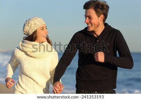Happy couple running on the beach in winter with the sea in the background - stock photo