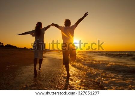 happy couple running on the beach on sunset - stock photo