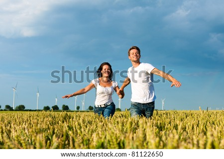Happy couple running over grainfield in summer hand in hand - stock photo