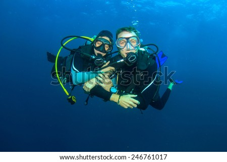 Happy couple scuba diving together - stock photo