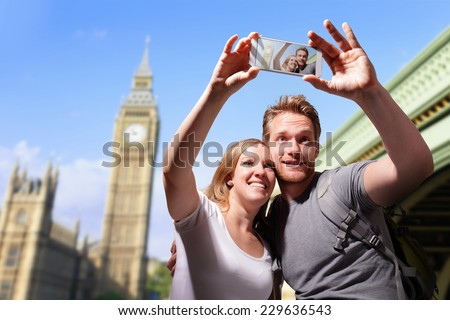 happy couple selfie by smart phone in london with big ben background, caucasian - stock photo